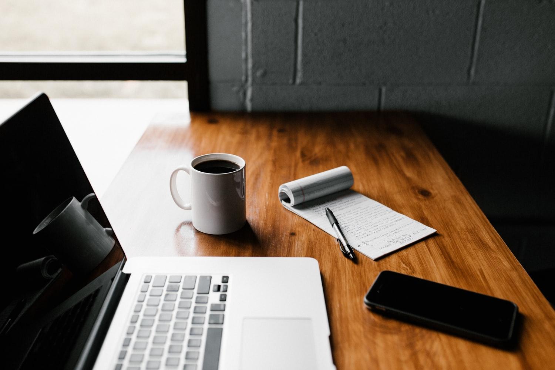 Dator, kaffe och penna på skrivbord